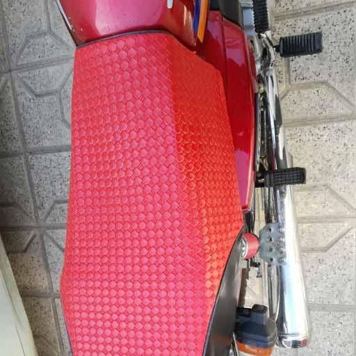 زین قرمز موتور سیکلت روی هوندا 125